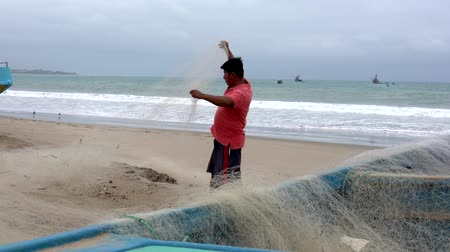 ügyesség : San Pedro, Ecuador - 20180915 -  Man Stands on Beach Next to Boat and Repairs Net