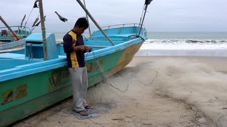 ügyesség : San Pedro, Ecuador - 20180915 -  Man Stands by Boat and Repairs Net Stock mozgókép