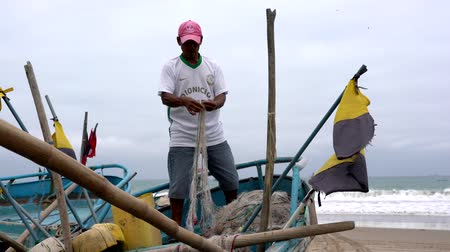 ügyesség : San Pedro, Ecuador - 20180915 -  Man Stands in Boat As He Fixes Net