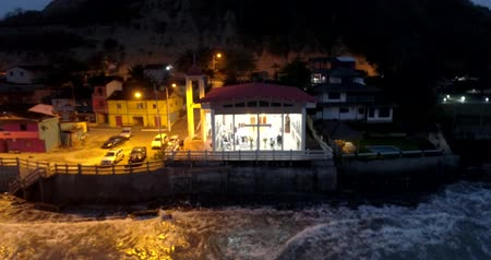 barışçı : La Entrada, Ecuador - 20180914 - Drone Aerial Time Lapse  -  Drone Approaches Glass Fronted Church With People Inside at Night at High Tide Stok Video