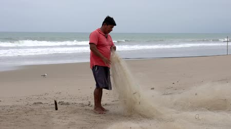 ügyesség : San Pedro, Ecuador - 20180915 -  Man Stands on Beach and Repairs Net
