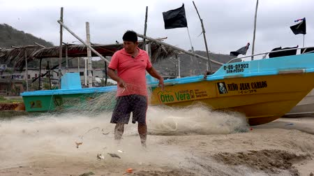 ecuador : San Pedro, Ecuador - 20180915  -  Beach View of Man Standing on Beach Next to Boat and Repairing Net