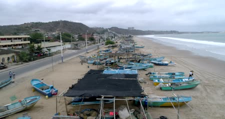 small vessels : San Pedro, Ecuador - 20180915 - Drone Aerial  -  Flight Along Beach Over Parked Fishing Boats and Fishermen Fixing Nets Stock Footage
