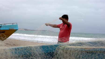 ügyesség : San Pedro, Ecuador - 20180915 -  Low View of Man Standing on Beach Next to Boat and Repairing Net