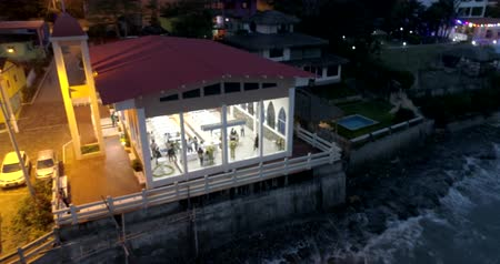 barışçı : La Entrada, Ecuador - 20180914 - Drone Aerial Time Lapse  -  Drone Pans Across Glass Fronted Church With People Inside at Night at High Tide