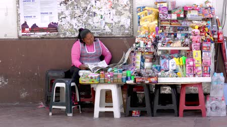 газета : Cuenca, Ecuador  -  20180920  -  Woman Sits By Her Table of Goods to Sell, Reading Newspaper As Person Walks Past Стоковые видеозаписи