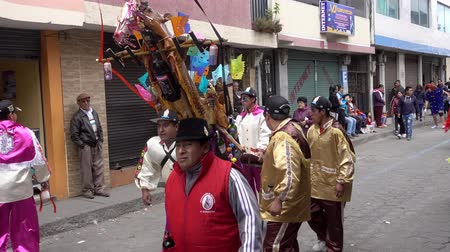 ecuador : Latacunga, Ecuador  -  20180925  -  Ashanguero in White Carries 250 Pounds of Feast on His Back in Mama Negra Parade