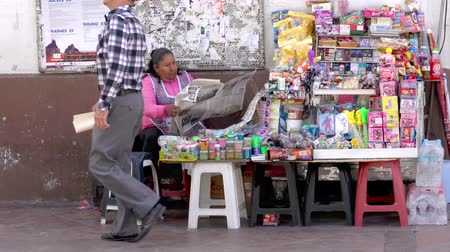 газета : Cuenca, Ecuador  -  20180920  -  Woman Sits By Her Table of Goods to Sell, Reading Newspaper Стоковые видеозаписи