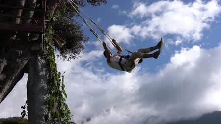 ecuador : Banos, Ecuador - 20180924 - Man Rotates On Casa de Arbol Swing Over Abyss Against Clouds Stock Footage