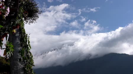 lano : Banos, Ecuador - 20180924 - Man Rides Casa de Arbol Swing Over Abyss Against Clouds