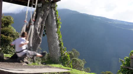 lano : Banos, Ecuador - 20180924 - Man Rides On Casa de Arbol Swing Over Abyss