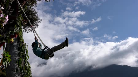 hluboký : Banos, Ecuador - 20180924 - Man Throws Arms Wide On Casa de Arbol Swing Over Abyss Against Clouds