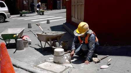 강화 : Cuenca, Ecuador  -  20180920  -  Worker Trowels Grout Around New Tiles in Sidewalk Repair