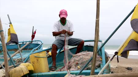 ügyesség : San Pedro, Ecuador - 20180915 -  Man Repairs Net While Sitting In Boat Stock mozgókép