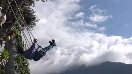 hluboký : Banos, Ecuador - 20180924 - Woman Rotates and Throws Arms Wide On Casa de Arbol Swing Over Abyss Against Clouds Dostupné videozáznamy