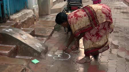 marigolds : Madurai, India - 20180308 -  Woman Draws Duck In Front Of House With Rice Powder