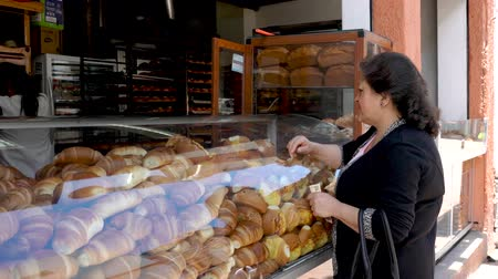 lokaal : Cuenca, Ecuador  -  20180920  -  Woman Buys Bread From Panaderia Bread Store Facing Street Stockvideo
