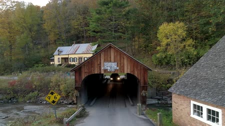 megye : Tunbridge, Vermont  -  20181009  -  Aerial Drone  -  Car Drives Through Mill Covered Bridge Built in 1883 Stock mozgókép