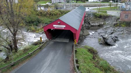 megye : Taftsville, Vermont  -  20181012  -  Aerial Drone  -  Bike Rides Out Then Car Drives In Waitsfield Covered Bridge in Vermont Stock mozgókép