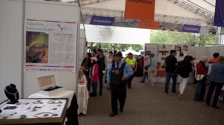 adil : Cuenca, Ecuador - 20181003 - Cuenca Independence Day Festival TimeLapse  -  Pan of Back Rows of Busy Vendor Tent Pavilion Starts With Jewelry Maker