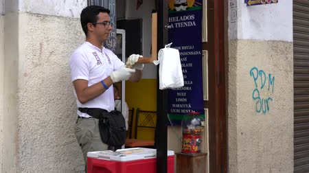 şekerleme : Cuenca, Ecuador - December 31, 2018 - Man makes salt water taffy and sells to woman customer Stok Video