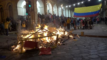 костер : Cuenca, Ecuador - December 31, 2018 - People watch street bonfire at midnight New Years Eve with Ecuadorian Flag in background