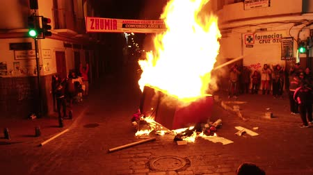 костер : Cuenca, Ecuador - December 31, 2018 - Bonfire is fed on a street at midnight on New Years Eve as people hug and celebrate