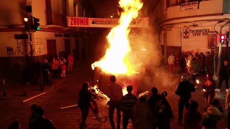 vonk : Cuenca, Ecuador - December 31, 2018 - Bonfire is fed on street at midnight at New Years Eve