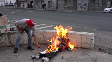 костер : Cuenca, Ecuador - December 31, 2018 - Family burns effigy representing bad from the Old Year as cars and pedestrians pass by Стоковые видеозаписи