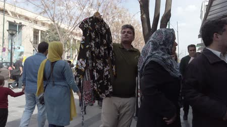 трейдер : Tehran, Iran - 2019-04-03 - Street Vendor Sells Shirts. Стоковые видеозаписи