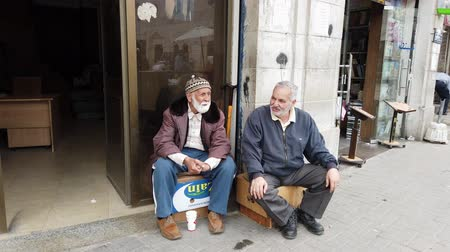 ülő : Amman, Jordan - 2019-04-18 - Two Elderly Men Sit on Boxes and Talk.
