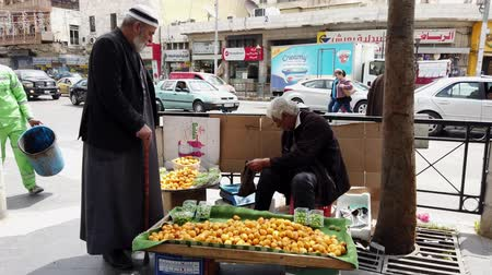 Ürdün : Amman, Jordan - 2019-04-18 - Street Vendor Sits on Crate And Makes a Sale of His Fruits.