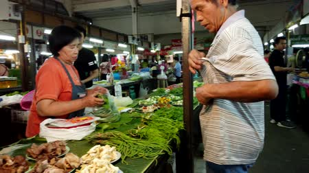 alku : Lampang, Thailand - 2019-03-07 - Market Vendor Makes a Sale of Greens.