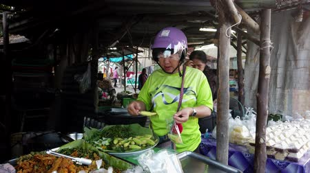 purchasing : Sukhothai, Thailand - 2019-03-06 - Woman Buys Baby Corn From Market Vendor.