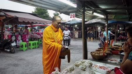adomány : Sukhothai, Thailand - 2019-03-06 - Monk Blesses Woman Vendor in Market.