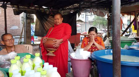 požehnat : Sukhothai, Thailand - 2019-03-06 - Man Makes Donation To Monk Who Then Blesses Two Vendors.