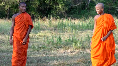 vallási : Haberna, Sri Lanka- 2019-03-22 - Two Young Monks Walk Towards Camera in Field Closeup.