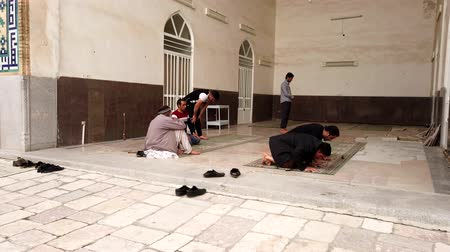 луки : Kerman, Iran - 2019-04-06 - Muslim Men Remove Their Shoes and Pray in Ganjali Mosque 2. Стоковые видеозаписи