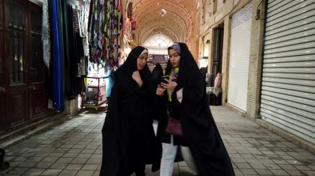 oryantal : Kashan, Iran - 2019-04-15 - Two Women in Hijab Talk and Look at Phone in Kashan Bazar.