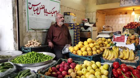 banan : Kashan, Iran - 2019-04-15 - Man Stands Near His Fruits That He Sells in Market.
