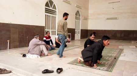 náboženství : Kerman, Iran - 2019-04-06 - Muslim Men Remove Their Shoes and Pray in Ganjali Mosque 3.