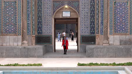 persie : Kerman, Iran - 2019-04-06 - Woman in Red Comes Out of Ganjali Mosque While Children Play in Background.