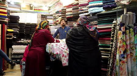 persiano : Kashan, Iran - 2019-04-15 - Two Women in Scarves Shop for Cloth.