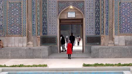 khan : Kerman, Iran - 2019-04-06 - Woman in Red Enters Ganjali Mosque While Mulahs Leave.