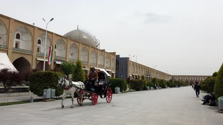 lő : Isfahan, Iran - 2019-04-12 - Horse Carriage Ride Around Naqshe Cehan Square 1 - Rider Uses For Phone For Video.