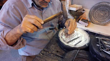 warsztat : Isfahan, Iran - 2019-04-12 - Elderly Man Uses Hammer and Chisel to Engrage Silver Bowl - Close. Wideo
