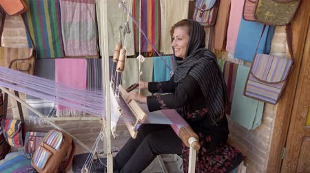 rode draad : Isfahan, Iran - 2019-04-12 - Young Woman Weaves Cloth 3 - Side View.