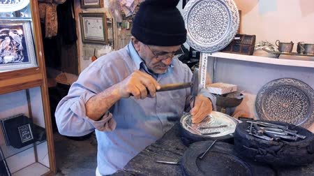 contornos : Isfahan, Iran - 2019-04-12 - Elderly Man Uses Hammer and Chisel to Engrage Silver Bowl - Long.
