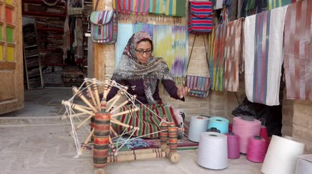 rode draad : Isfahan, Iran - 2019-04-12 - Woman Spins Yarn 4 - Low View. Stockvideo