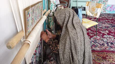 kelet : Isfahan, Iran - 2019-04-12 - Elderly Woman Weaves Carpet 3 - High. Stock mozgókép